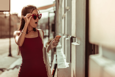 Shocked woman. Dark-haired slim hot nice-appealing bewitching woman in trendy eyeglasses and red dress feeling shocked while walking the streets Banco de Imagens