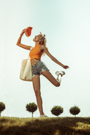 Jumping with the watermelon. Happy contended vigorous active slim alluring appealing bewitching woman wearing shorts and top jumping up with the watermelon