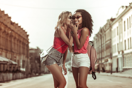 Whispering in ear. Delightful dazzling nice-appealing charming slim fair-haired young-adult lady whispering in ear of her curly-haired Afro-American charming girlfriend wearing eyeglasses outdoors. 版權商用圖片