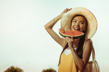 Eating watermelon. Face-portrait of dazzling beautiful smiling cheerful lovely lady with long dark hair and straw hat eating the watermelon Banco de Imagens