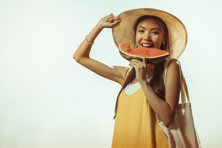 A woman with watermelon piece. Face-portrait of bewitching beautiful radiant cheerful pretty young-adult woman with long dark hair wearing straw hat and eating the watermelon.