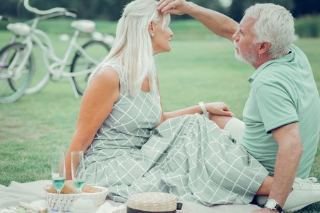 My love. Nice aged man sitting together with his wife while fixing her hair Imagens - 124984337