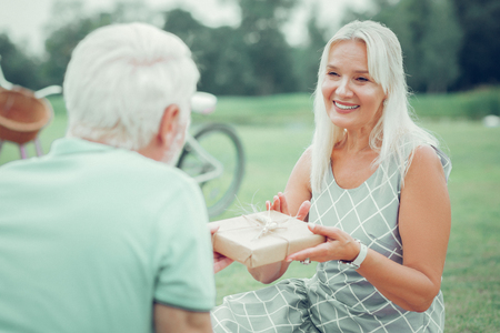 Happy anniversary. Beautiful nice woman giving present to her husband while congratulating him on their anniversary Imagens - 124984340