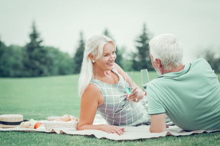 Wonderful picnic. Nice positive woman smiling to her husband while drinking champagne together with him Imagens - 124984343