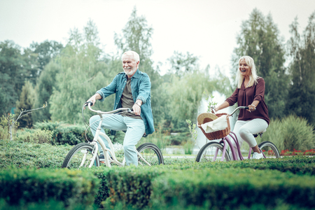 On bicycles. Joyful nice people feeling happy while enjoying their bicycle ride together Imagens - 124984344