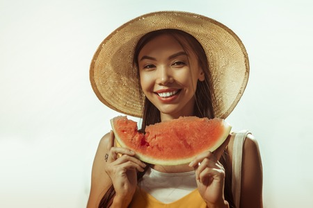 Watermelon piece in hands. Close-up face portrait of alluring pleasing beaming smiling contended dark-haired woman in early 25s keeping watermelon piece in hands.