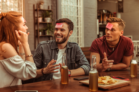 Cheerful friends. Happy cheerful contended smiling beaming joyous nice-looking vigorous young-adult three friends sharing a laugh at the bar and playing a hedbanz together