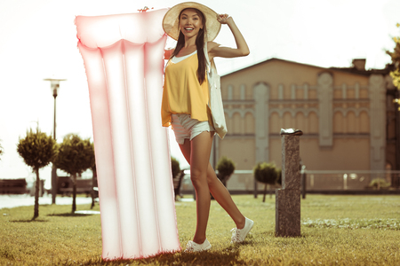 Pink mattress. Bewitching dazzling smiling beaming glowing long-haired joyful beauty wearing hat and yellow top standing with a pink inflatable air mattress outdoors. Banco de Imagens