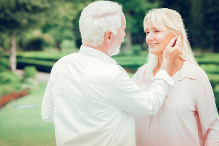 Romantic moments. Delighted nice man touching his wifes cheek while standing with her in the park