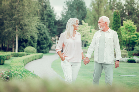 Romantic walk. Delighted happy couple holding their hands while walking together in the park Imagens