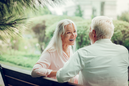 Great mood. Cheerful delighted woman looking at her husband while laughing together with him