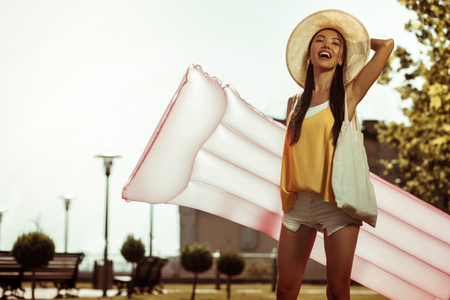 Going to the beach. Contended appealing slim hot arresting alluring long-haired young-adult female going to the beach with a pink air mattress for swimming. Stock Photo