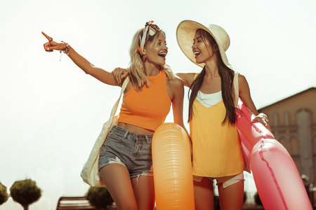 Going to the beach. Beautiful pretty alluring beaming radiant cheerful joyous women wearing beach clothing laughing and holding swim rings in hands