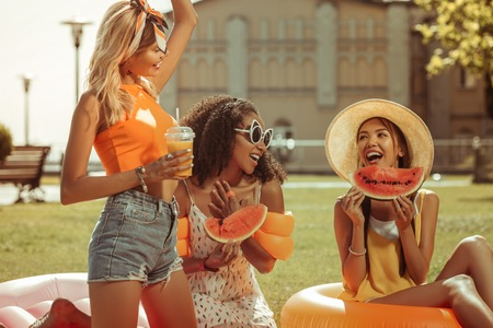 Having fun outdoors. Energetic contended vigorous active smiling nice-looking beaming lovely three girls having fun during a picnic with fruits outdoors.