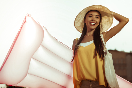 Preparation for a swimming. Happy contended nice-looking appealing charming delightful glowing dark-haired smiling woman wearing hat holding an inflatable air mattress for swimming