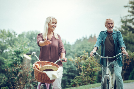 Active lifestyle. Positive active couple talking to each other while riding bikes together Imagens - 124984156
