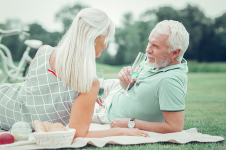 Delicious drink. Pleasant aged couple looking at each other while enjoying their champagne together Reklamní fotografie