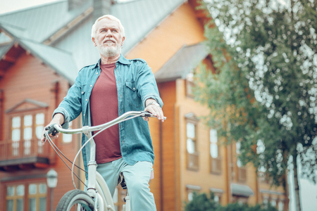 My hobby. Nice bearded man being in front of his house while riding a bicycle