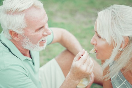 Caring husband. Joyful aged man feeding his wife while caring about her Imagens