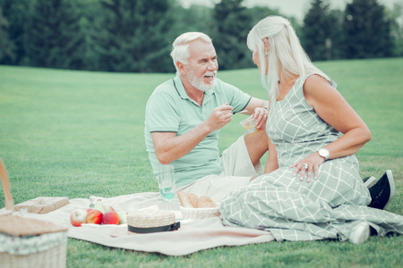 In nature. Pleasant aged couple feeling happy while enjoying their romantic picnic Imagens