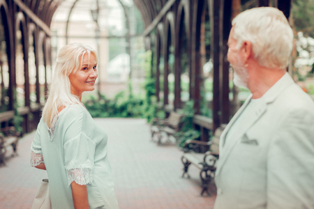 Beautiful smile. Joyful aged woman smiling to her man while walking away from him Imagens - 124984195