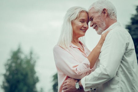 Loving couple. Pleasant aged couple hugging each other while being still in love