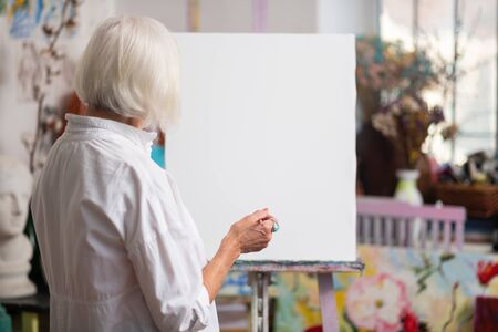 Near white canvas. Blonde-haired aged woman standing near white canvas before painting