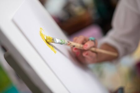 Bright yellow. Close up of painting brush with bright yellow gouache in hands of artist