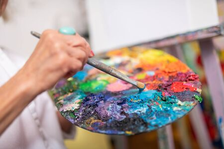 Painting brush. Close up of aged woman holding painting brush and color palette Banco de Imagens