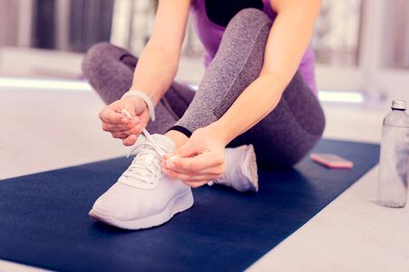 Time to relax. Sporty woman making her shoes while going to stretch her legs Stock Photo - 124983601