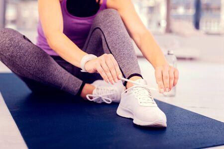 Scarpe preferite. Rilassata giovane donna seduta sul tappeto mentre allaccia le sue scarpe da ginnastica