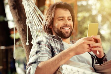 Digital technology. Joyful handsome man smiling while looking at his smartphone screen