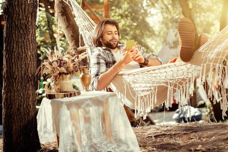 Internet addiction. Delighted handsome man lying with his smartphone in the hammock while browsing the Internet