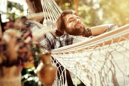 So comfortable. Nice happy man smiling while sleeping in the hammock Stock Photo