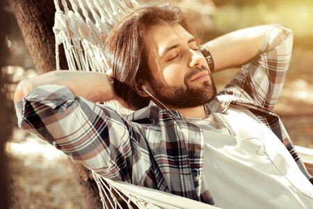 Perfect relaxation. Joyful handsome man listening to music while sleeping in the hammock
