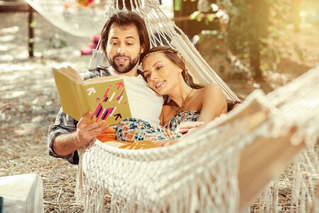 Romantic moments. Nice handsome man reading a book with his girlfriend while lying with her in a hammock