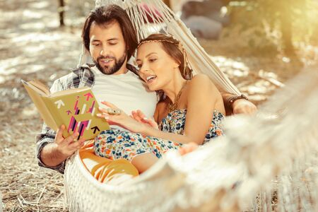 Being outdoors. Joyful romantic couple lying in a hammock while reading a book together