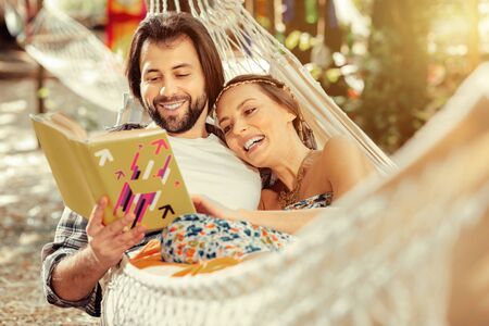 Pleasant entertainment. Happy positive couple smiling while reading a funny story together