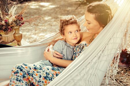 Close person. Positive nice boy looking at his mother while lying together with her in a hammock 免版税图像