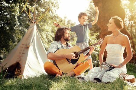 Pleasant music. Nice handsome man holding a guitar while playing songs for his family