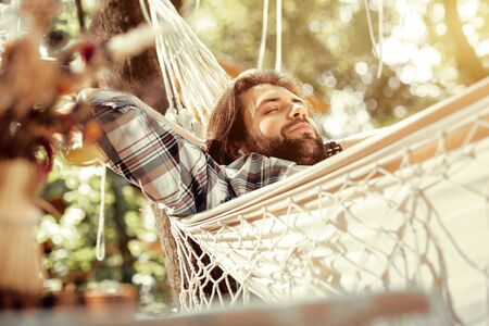 Best place. Nice handsome man sleeping while lying in the hammock Stock Photo