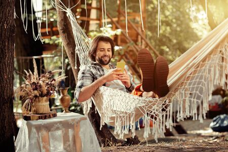 Online communication. Nice bearded man typing a message on his smartphone while resting in a hammock Stock fotó