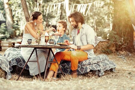 Care and love. Delighted nice woman feeding her son while sitting with him at the table Stock Photo