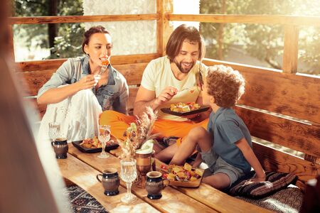 Extremely delicious. Happy delighted man smiling while feeding his son with salad Stock Photo