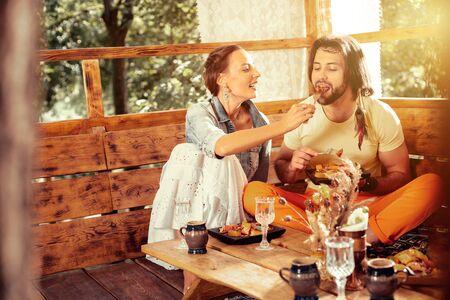 Caring wife. Nice joyful woman feeding her husband while caring about him