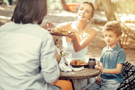 Meal time. Joyful nice woman holding a plate while giving food to her husband Stock Photo