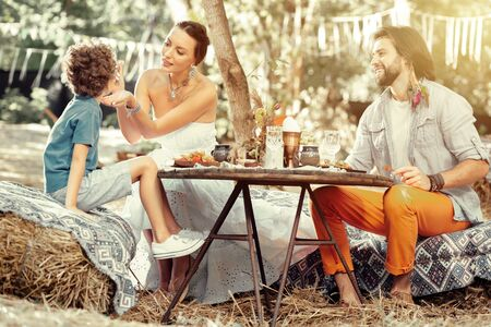 Outdoor meal. Positive delighted family sitting around the table while having a meal outdoors