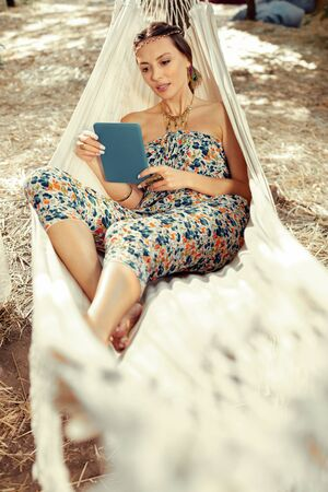Electronic device. Nice young woman looking at the tablet screen while resting in a hammock