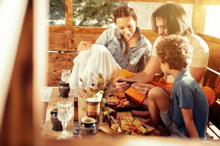 So interesting. Nice joyful family sitting together while watching an interesting video Stock Photo
