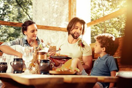 Family meal. Pleasant cute boy listening to his father while having a meal with his family
